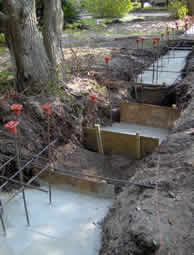 The trench is widened and the footing is poured along the length of the wall except where the larger lateral roots are located